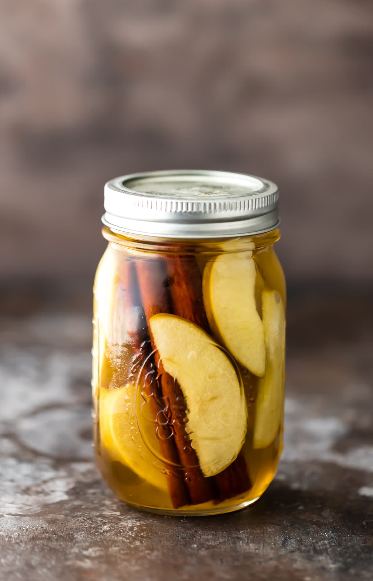 Receta casera de vodka: un tarro de albañil lleno de rodajas de manzana, palitos de canela y vodka