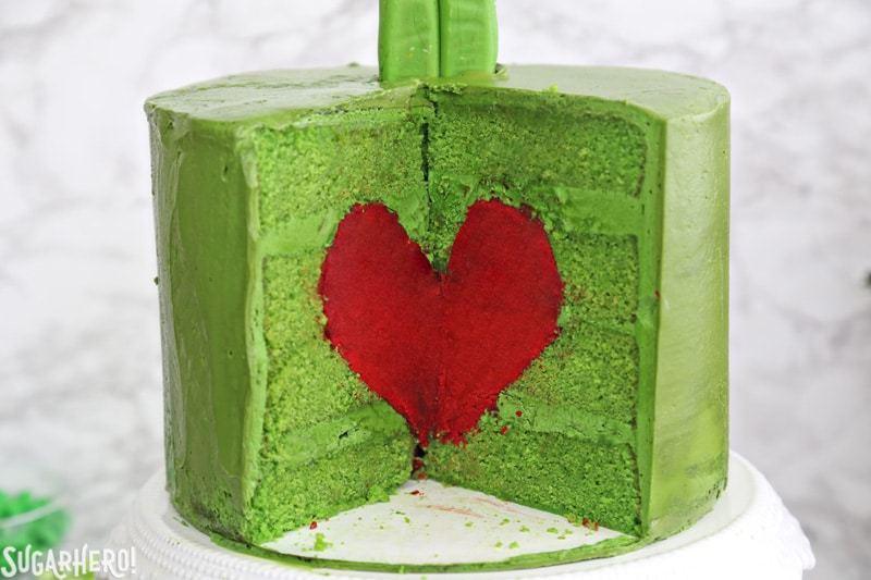 Pastel Grinch: primer plano del interior del pastel Grinch verde, que contiene un corazón de pastel rojo brillante   De SugarHero.com