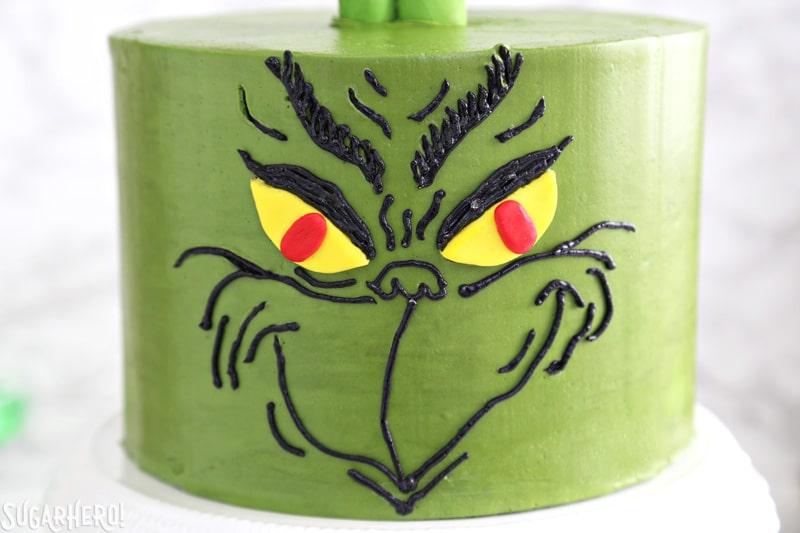 Pastel Grinch: primer plano de la cara del Grinch, hecho con crema de mantequilla negra sobre un pastel verde   De SugarHero.com