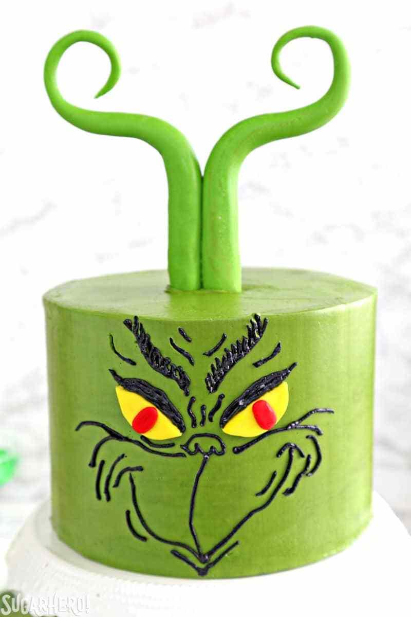 Pastel de Grinch: foto más cercana de la cara de Grinch colocada en un pastel verde con cabello fondant   De SugarHero.com
