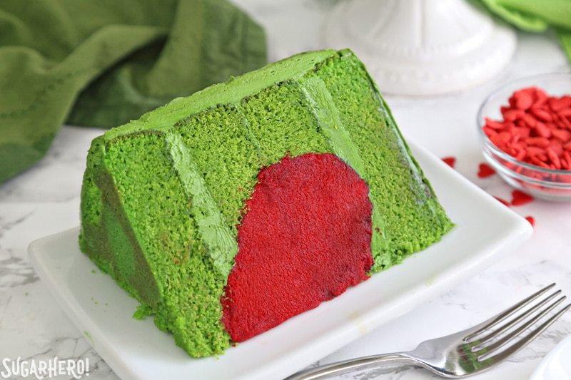 Pastel Grinch - primer plano de una rebanada de pastel Grinch, hecho de capas de pastel verde y un corazón rojo brillante en el interior   De SugarHero.com