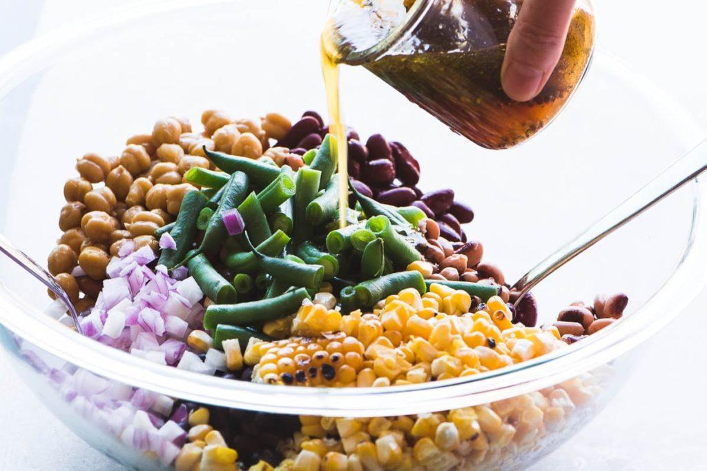 Verter el aderezo sobre ensalada de frijoles y maíz carbonizados