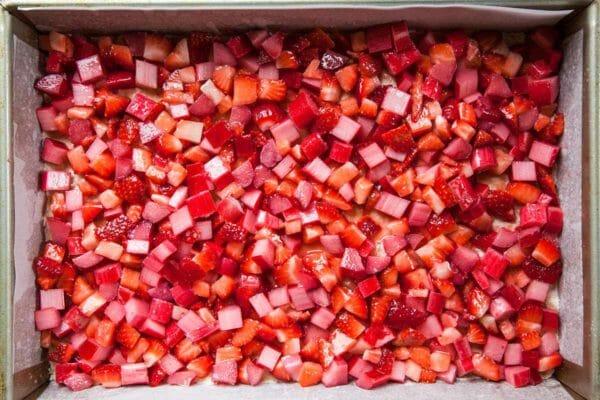 Strawberry Crumble Bars con ruibarbo extiende los ingredientes en la sartén