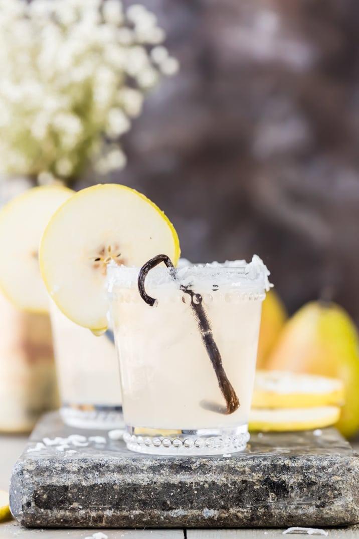 cóctel bordeado con hojuelas de coco y adornado con una rodaja de pera y vainilla