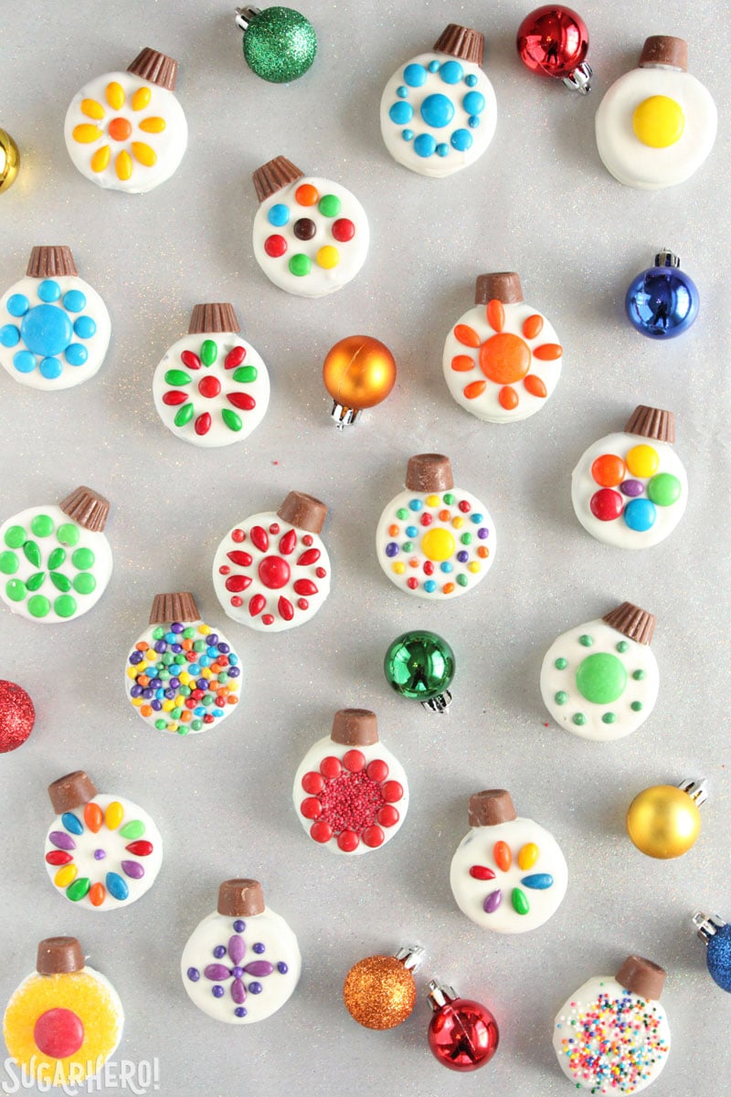 Adornos navideños de galletas Oreo: galletas navideñas brillantes y coloridas dispuestas con adornos alrededor | De SugarHero.com