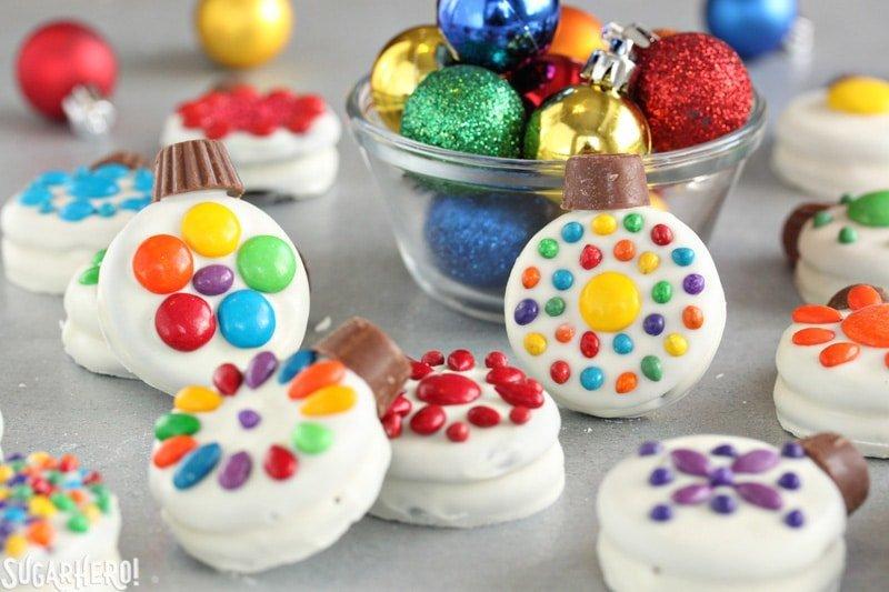 Adornos navideños de galletas Oreo: galletas Oreo decoradas como adornos navideños, con adornos reales en un tazón cercano | De SugarHero.com