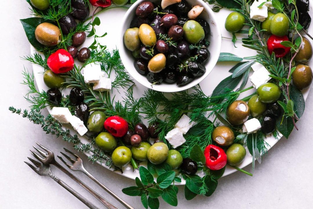 Guirnalda de aperitivo de oliva y hierbas en una bandeja blanca con tenedores de cóctel