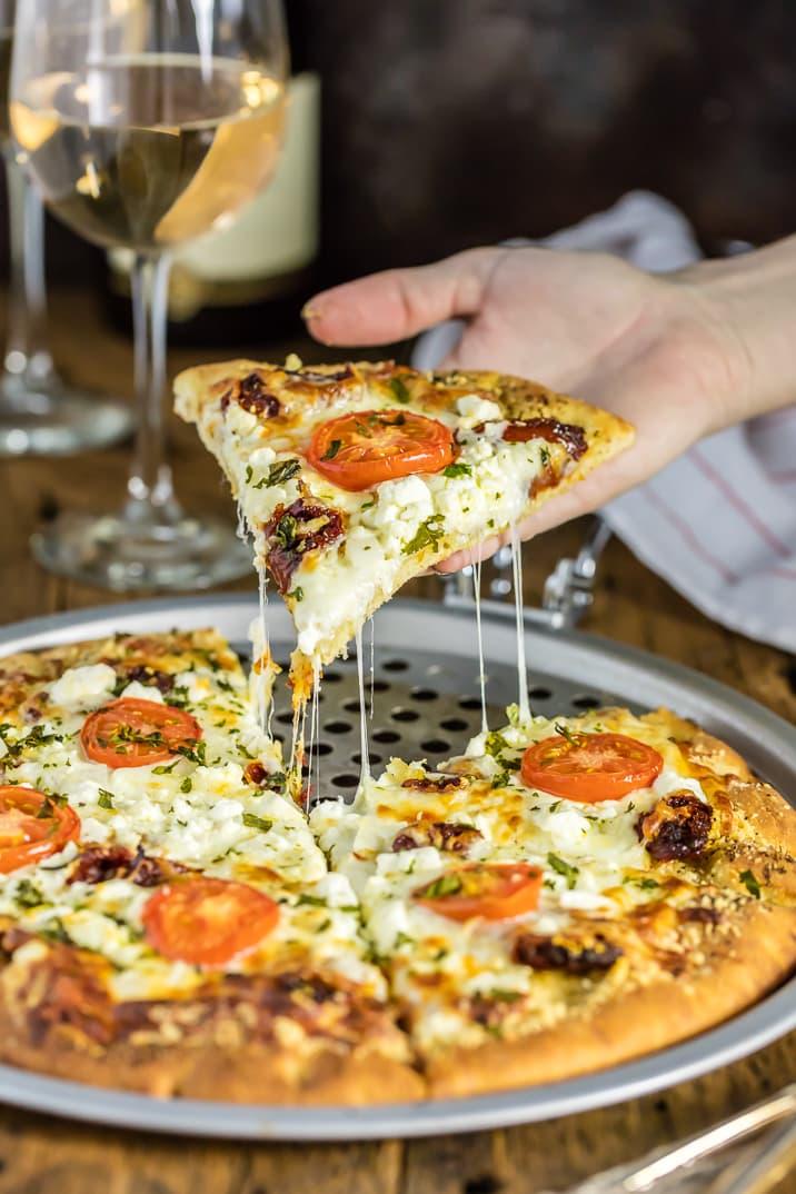 Pan de pizza blanca gourmet fácil con una rodaja, una copa de vino en segundo plano.