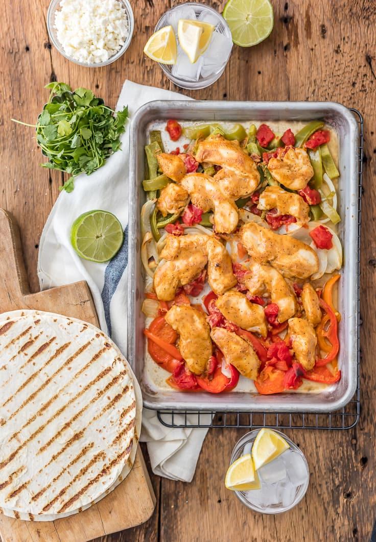 sartén fajitas de pollo en una mesa de madera, rodeada de tortillas, bebidas y tazones de ingredientes