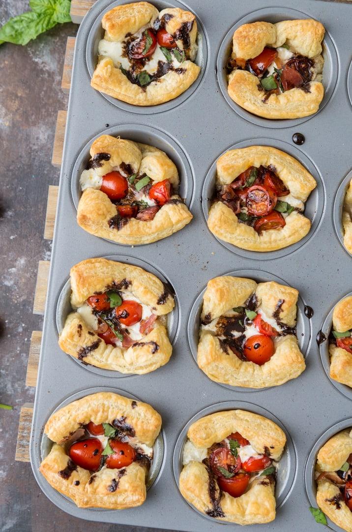 ¡Tazas Caprese de hojaldre! Nos encantan estos fríos y calientes. Reducción de tomate, mozzarella, jamón serrano, albahaca y balsámico. ¡PERFECCIÓN!