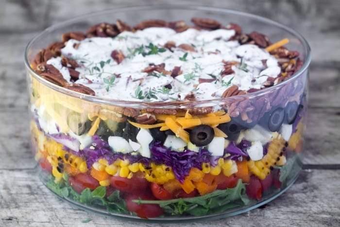 Fácil de montar y saludable Ensalada en capas de arco iris se puede hacer una cabeza antes de un picnic, comida compartida o barbacoa.