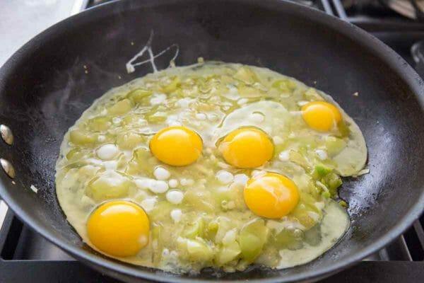 agregue los huevos a los tomatillos y las cebollas en la sartén