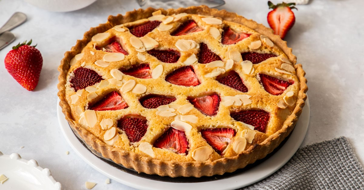 birdseye view of a strawberry tart on a white plate.
