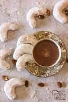 Galletas de almendras con una taza de chocolate caliente.