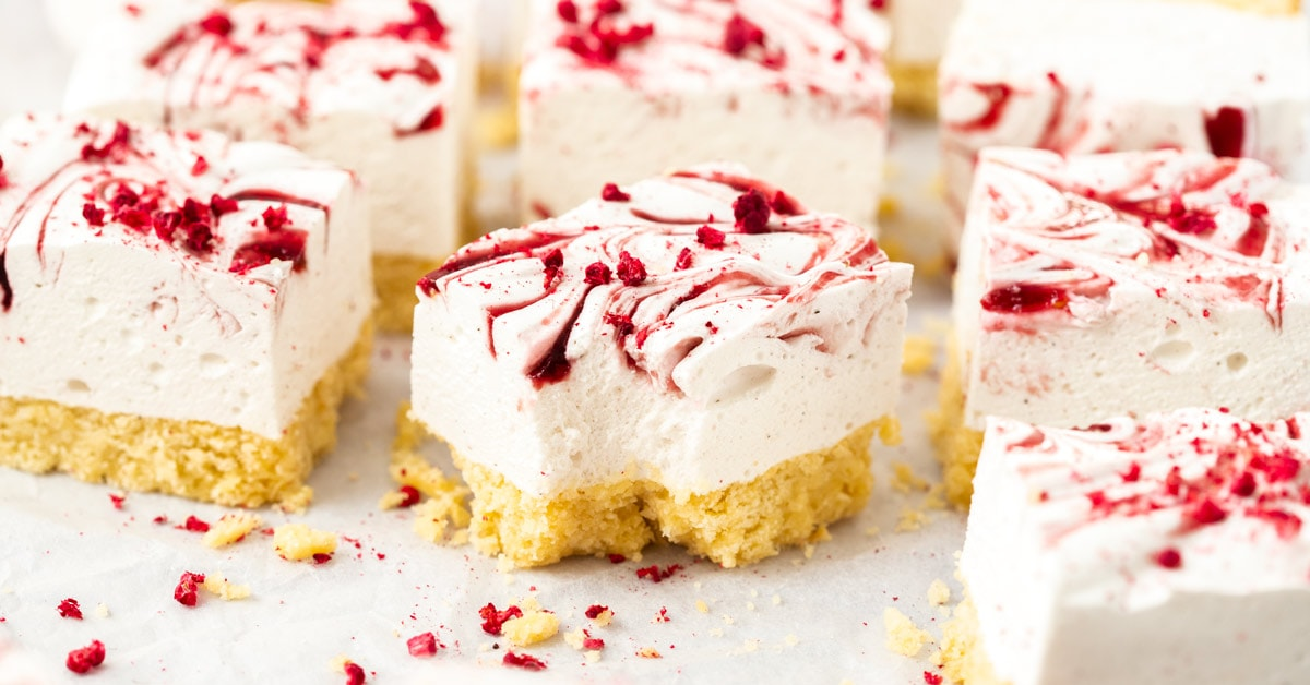 9 squares of marsmallow slice on a crumpled piece of white baking paper. freeze dried raspberries scattered around and a spoon covered in jam
