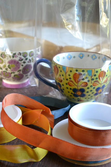 Envolviendo malvaviscos de vainilla caseros en tazas decorativas con celofán y cintas