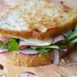 Sandwich de queso cheddar tostado, jamón y rúcula