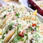 Estos tacos de salmón están cubiertos con salsa casera y salsa de aguacate y acentuados con cilantro fresco. ¡Estos sabrosos tacos de pescado son perfectos para una multitud!