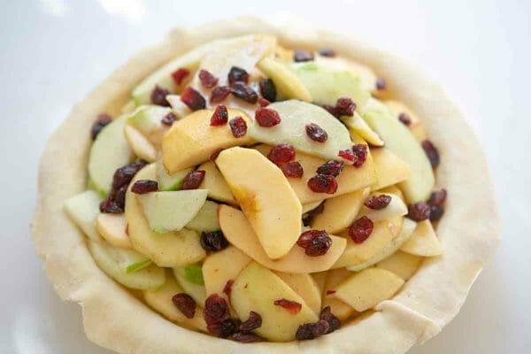 tarta de manzana y arándano rellenando la corteza