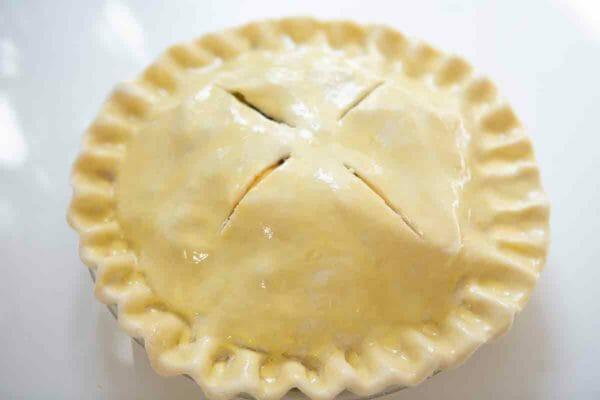 tarta de manzana y arándano cepillada con huevo y a punto de entrar al horno