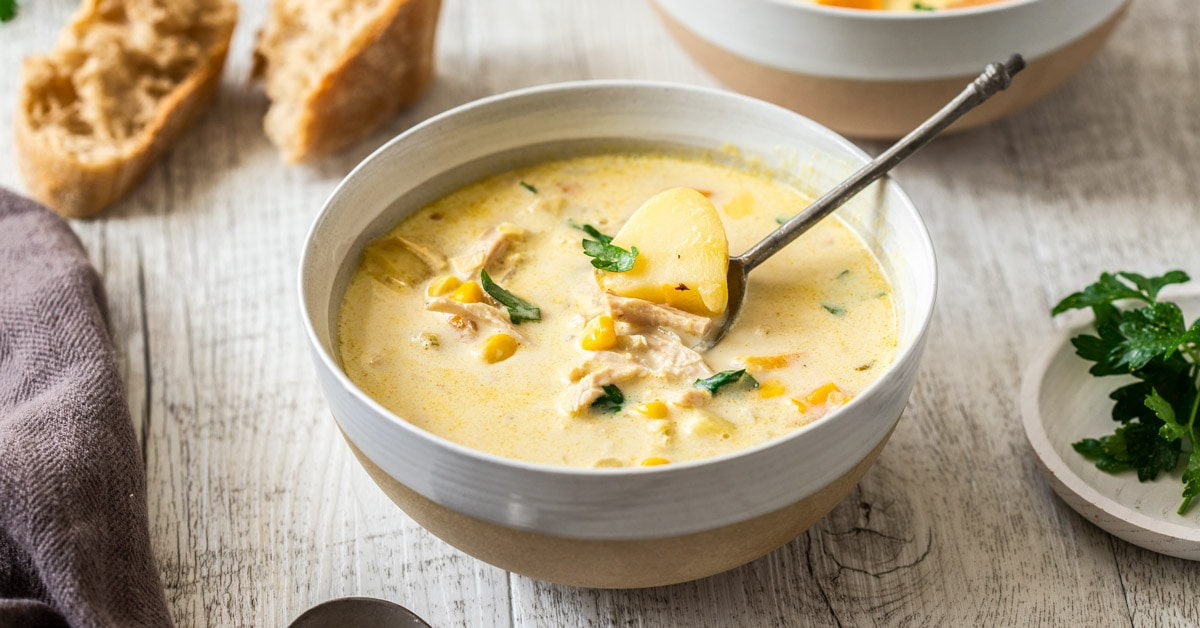 A bowl of turkey corn chowder with another in the background. On a white wooden tabletop