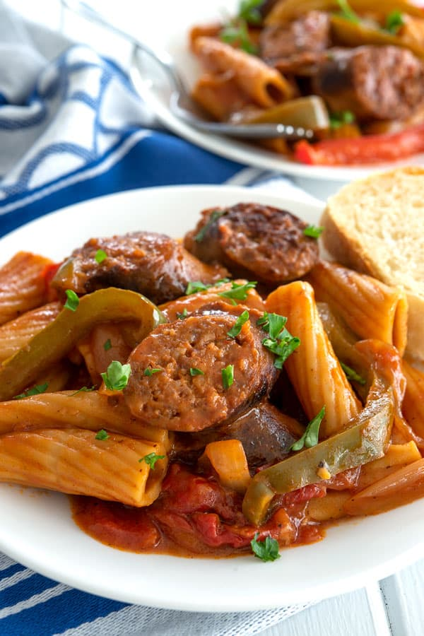 Sausage and peppers pasta on a plate with a side of Italian bread