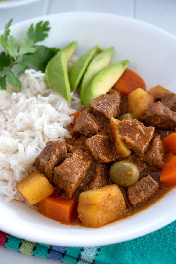 Carne Guisada puertorriqueña servida con arroz y aguacate en rodajas