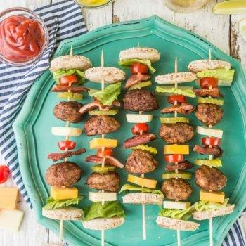 ¡Brochetas de hamburguesa con queso y tocino deconstruidas! Un aperitivo tan divertido y lindo a la parrilla para el verano. ¡Cargado con albóndigas, queso, tocino y todas las guarniciones de una gran hamburguesa!