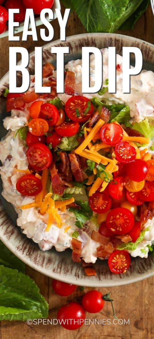 Un cuenco lleno de BLT Dip. Cubierto con tocino, lechuga, tomates y queso rallado.