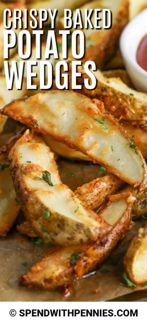 Ciérrese para arriba de las cuñas cocidas de la patata en una bandeja para hornear con la salsa de tomate.