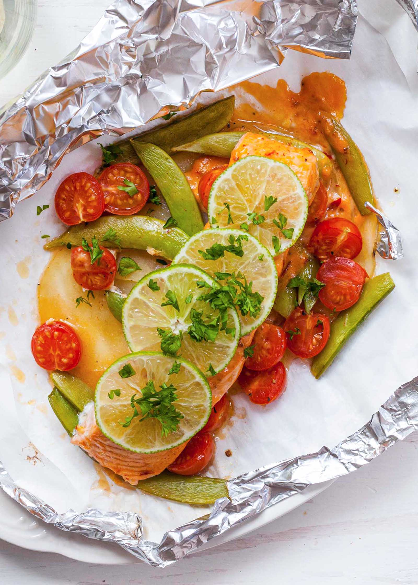 Top view of the best healthy salmon. A fillet is in the middle of an open foil packet with grape tomatoes, sugar snap peas, and sauce around it. Thinly sliced limes and chopped cilantro are on top of the salmon.