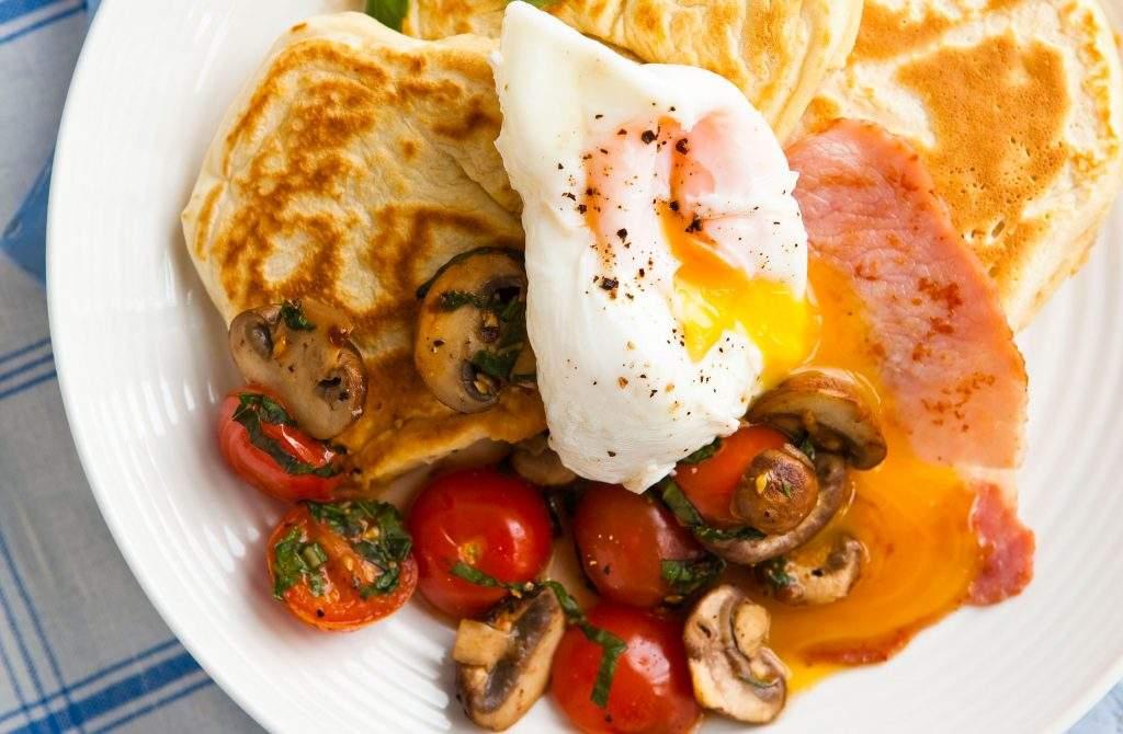 Panqueques de desayuno Los panqueques de desayuno durante todo el día usan una receta básica de panqueques y los sirven con tiras de tocino suculentas, huevo y tomates frescos.