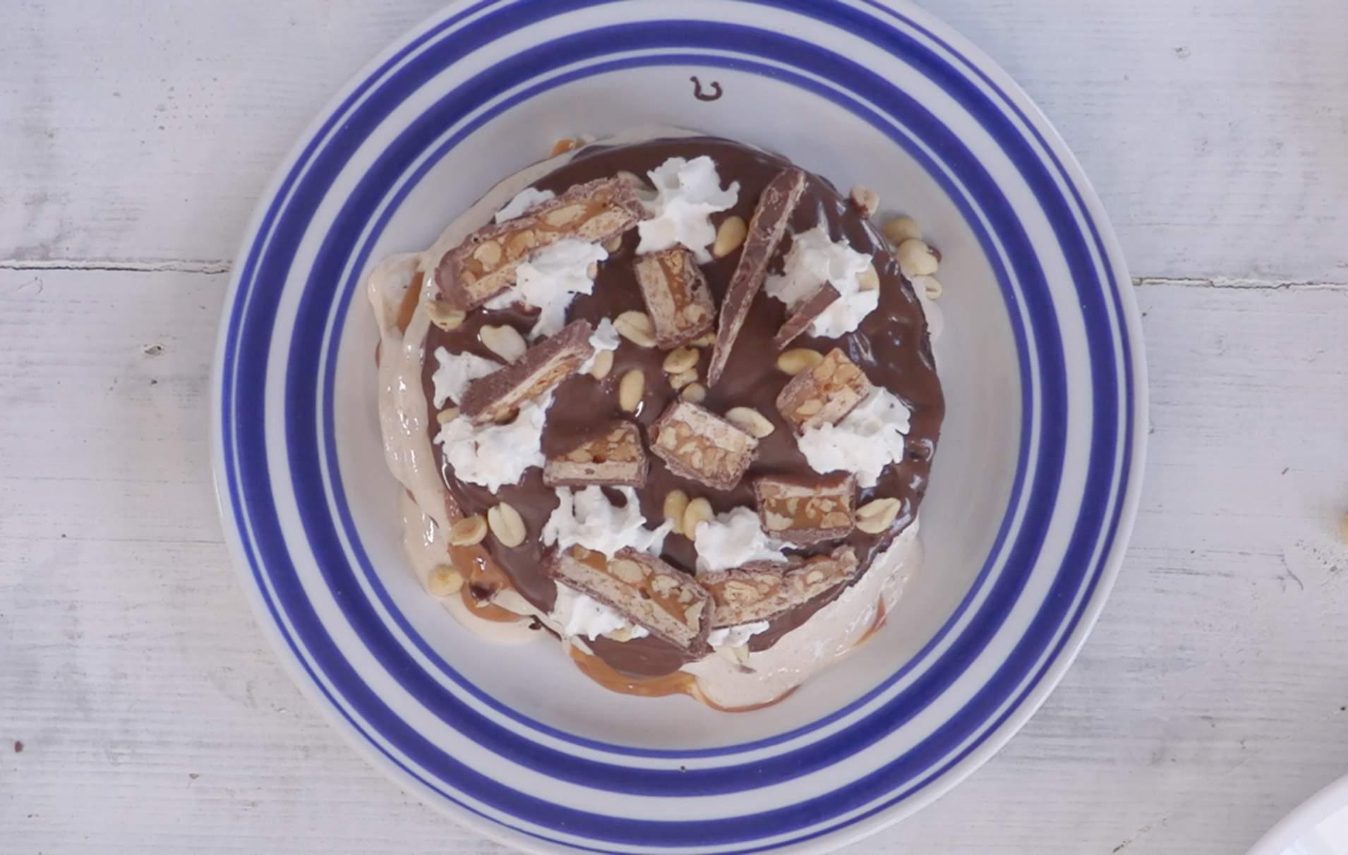 Snickers bar panqueques Si te gusta la barra Snickers, te ENCANTARÁ este panqueque lleno de turrón, caramelo, nueces, chocolate para untar, crema batida y, por supuesto, barras Snickers.