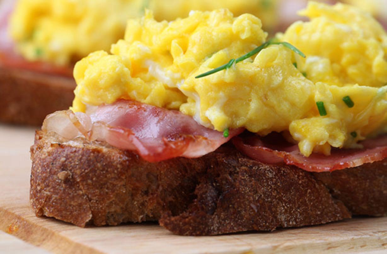 Huevos revueltos con queso y tocino Estos huevos revueltos con tocino y queso hacen un delicioso desayuno saludable servido con tostadas integrales.