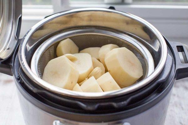 Coloque la canasta vaporera de papas en rodajas en el inserto de olla instantánea para hacer puré de papas