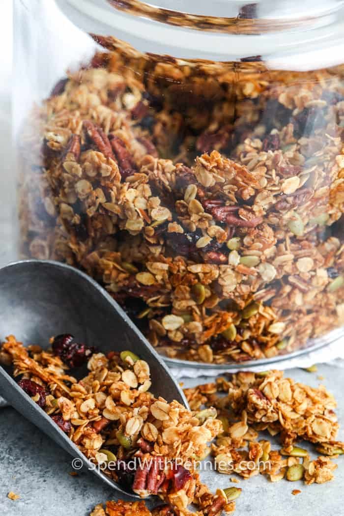 Homemade Granola in a glass jar with some in a metal scoop beside