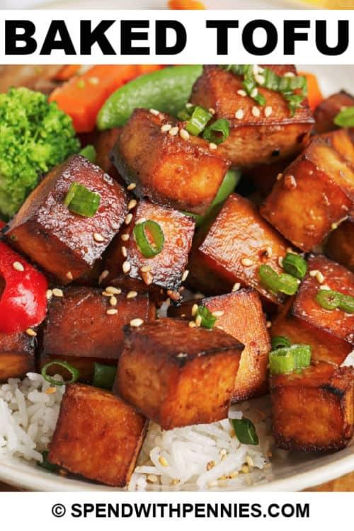 Cerca de tofu horneado servido sobre arroz con escritura