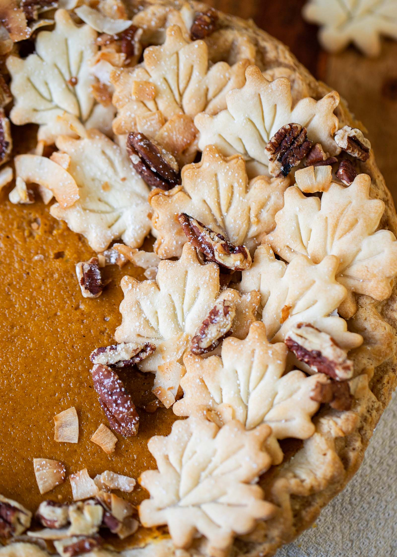 Leaves and pecans decorate the side of a pie for Thanksgiving family ideas.