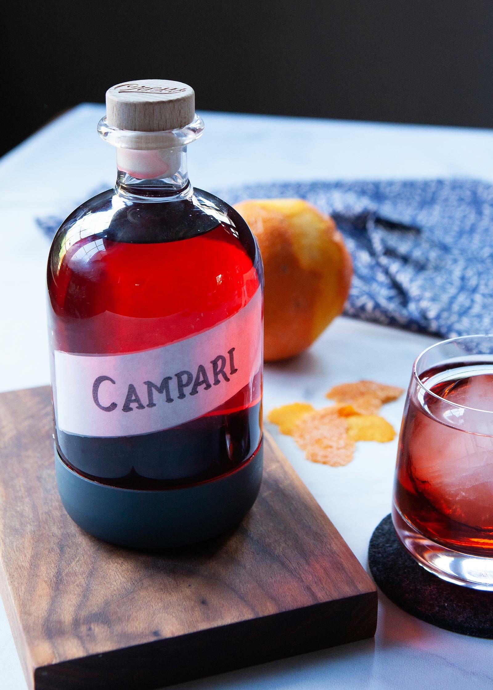 Homemade campari in a glass jar and set on a wooden board.