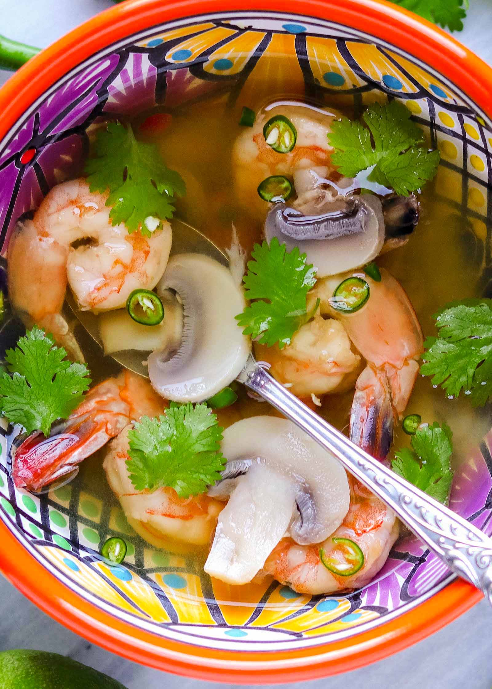Thai soup with shrimp in a brightly patterned bowl and spoon. Cilantro, shrimp, peppers, mushrooms and a light broth are in the bowl.