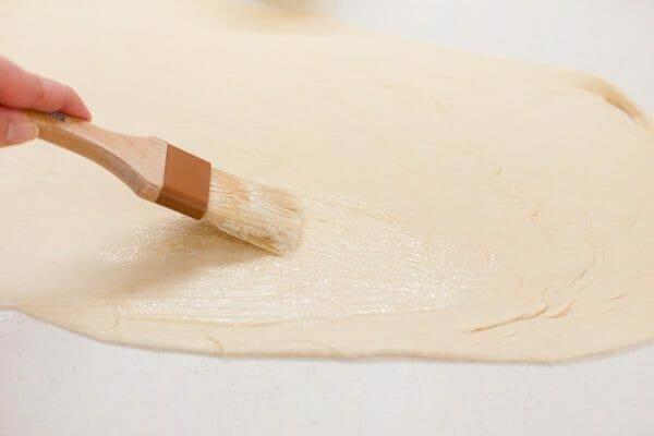 Cómo hacer rollos de la casa del león untando la masa enrollada con mantequilla.