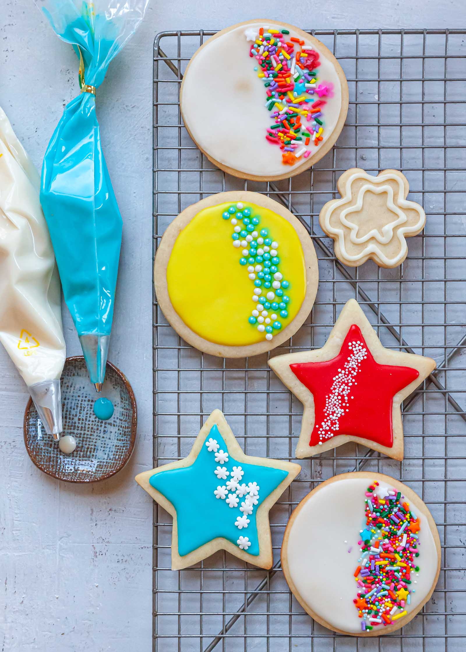 Two piping bags filled with Royal icing are set next to a cooling rack with decorated sugar cookies on it.