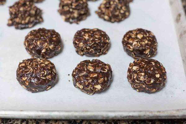 Galletas de chocolate sin hornear que se enfrían en una bandeja para hornear forrada de pergamino.