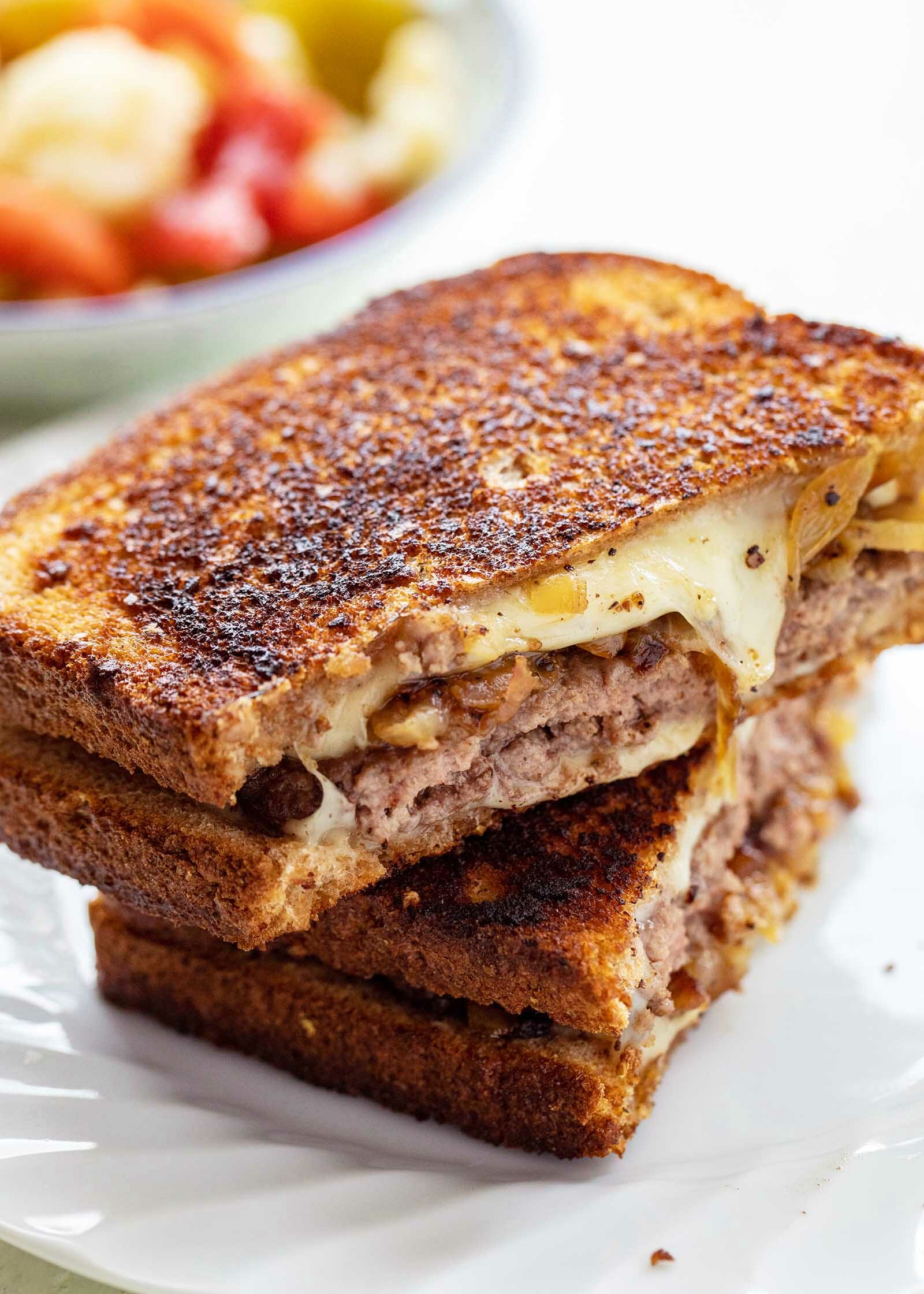 The best patty melt sliced in half and stacked on top of each other. The sandwich is crispy with melted cheese, caramelized onions and beef patties visible.