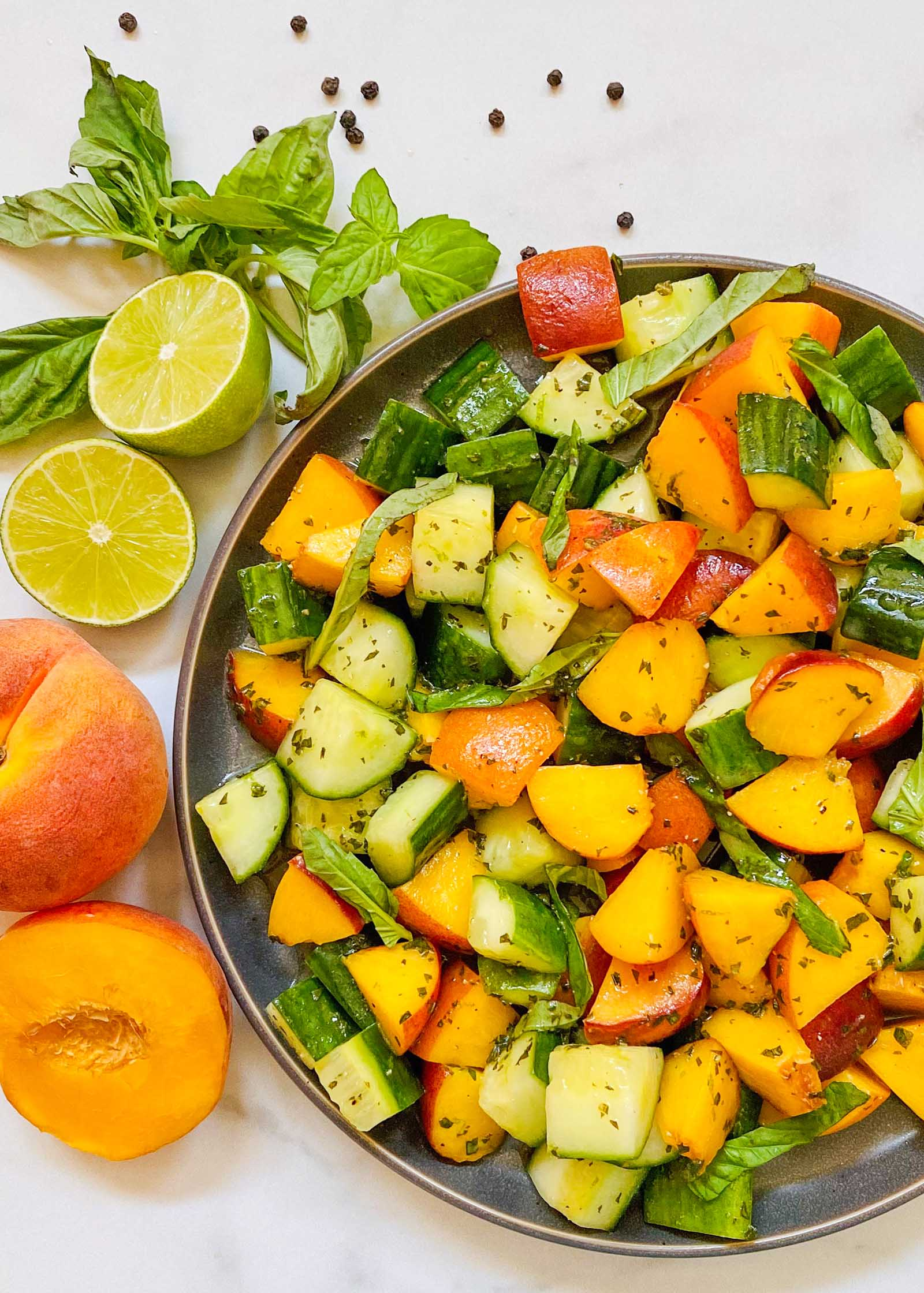 Refreshing summer salad made with peaches and cucumbers in a bowl with peaches, limes and basil to the left.