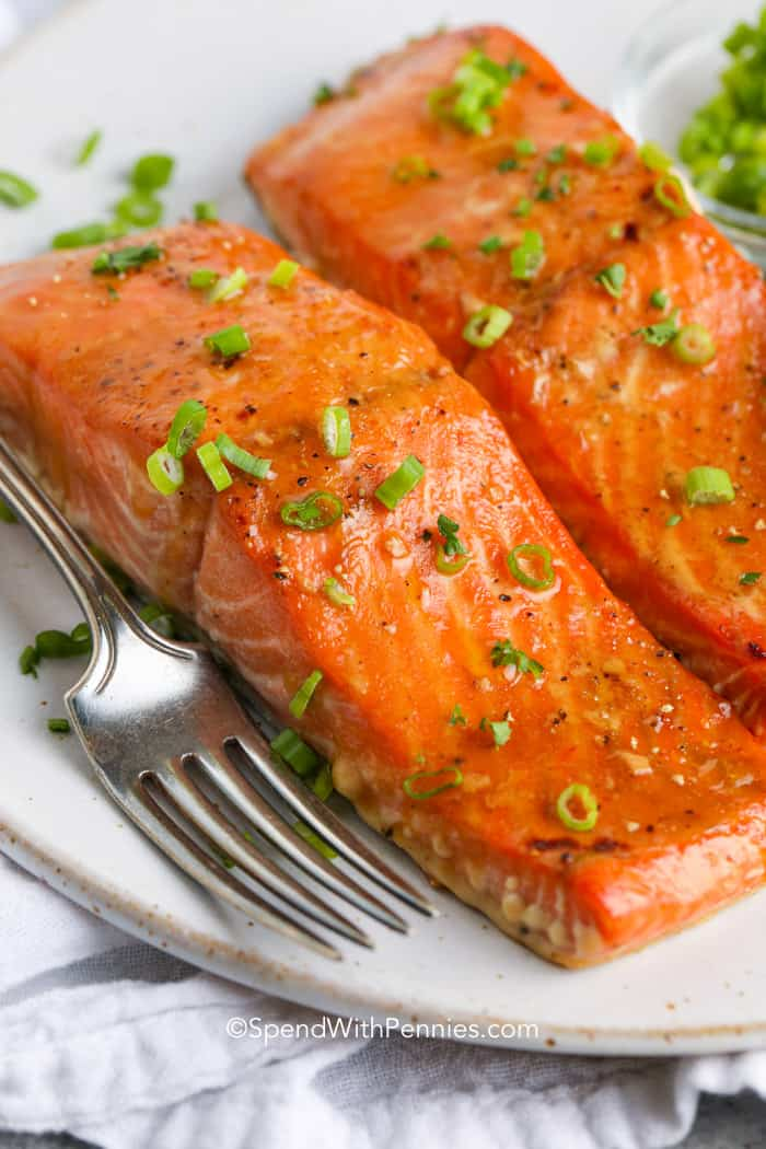 Baked salmon filets with a fork on a plate topped with green onions