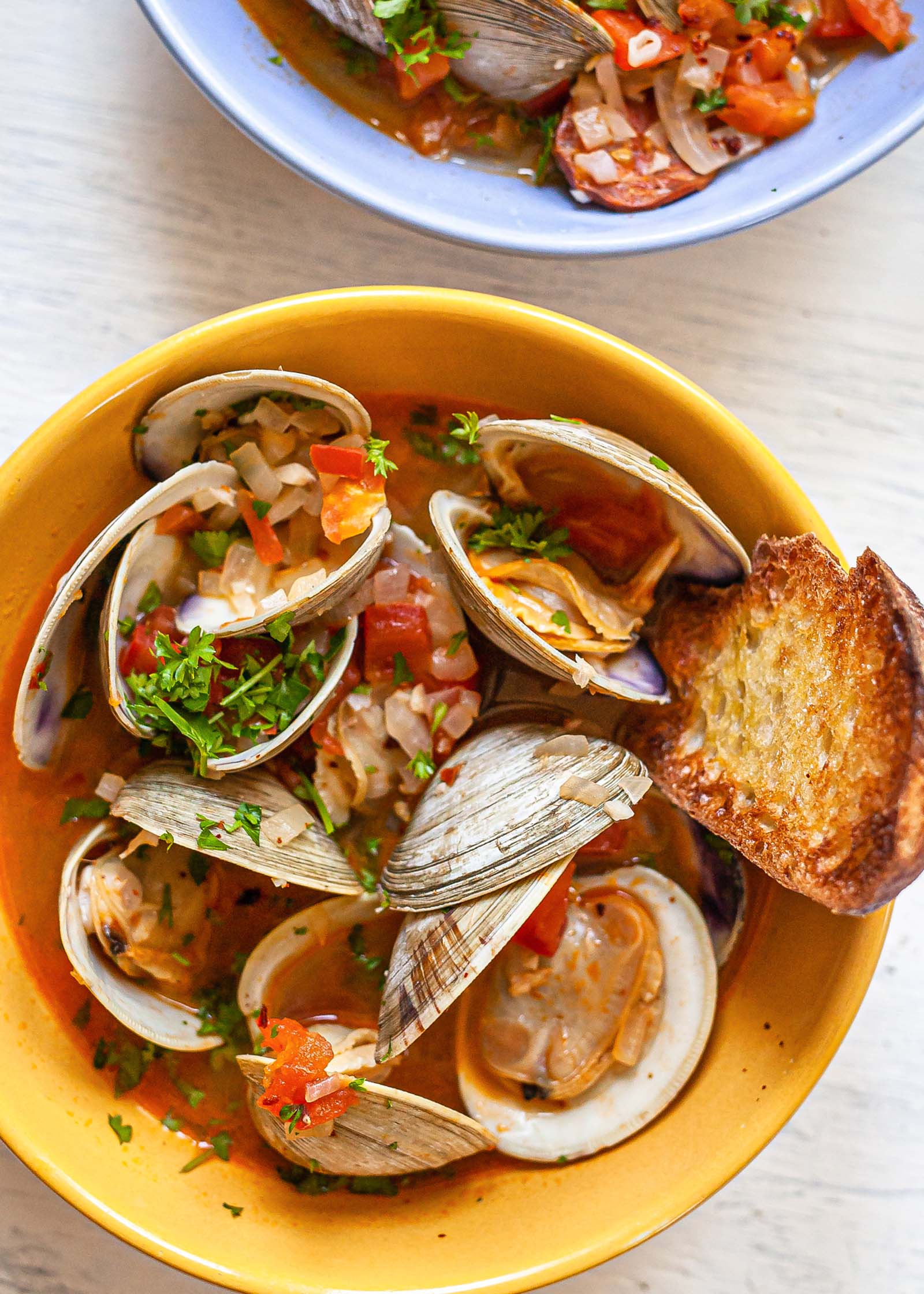 Overhead view of a yellow bowl with steamed clams with chorizo and grilled bread. A second blue bowl is partially visible above.