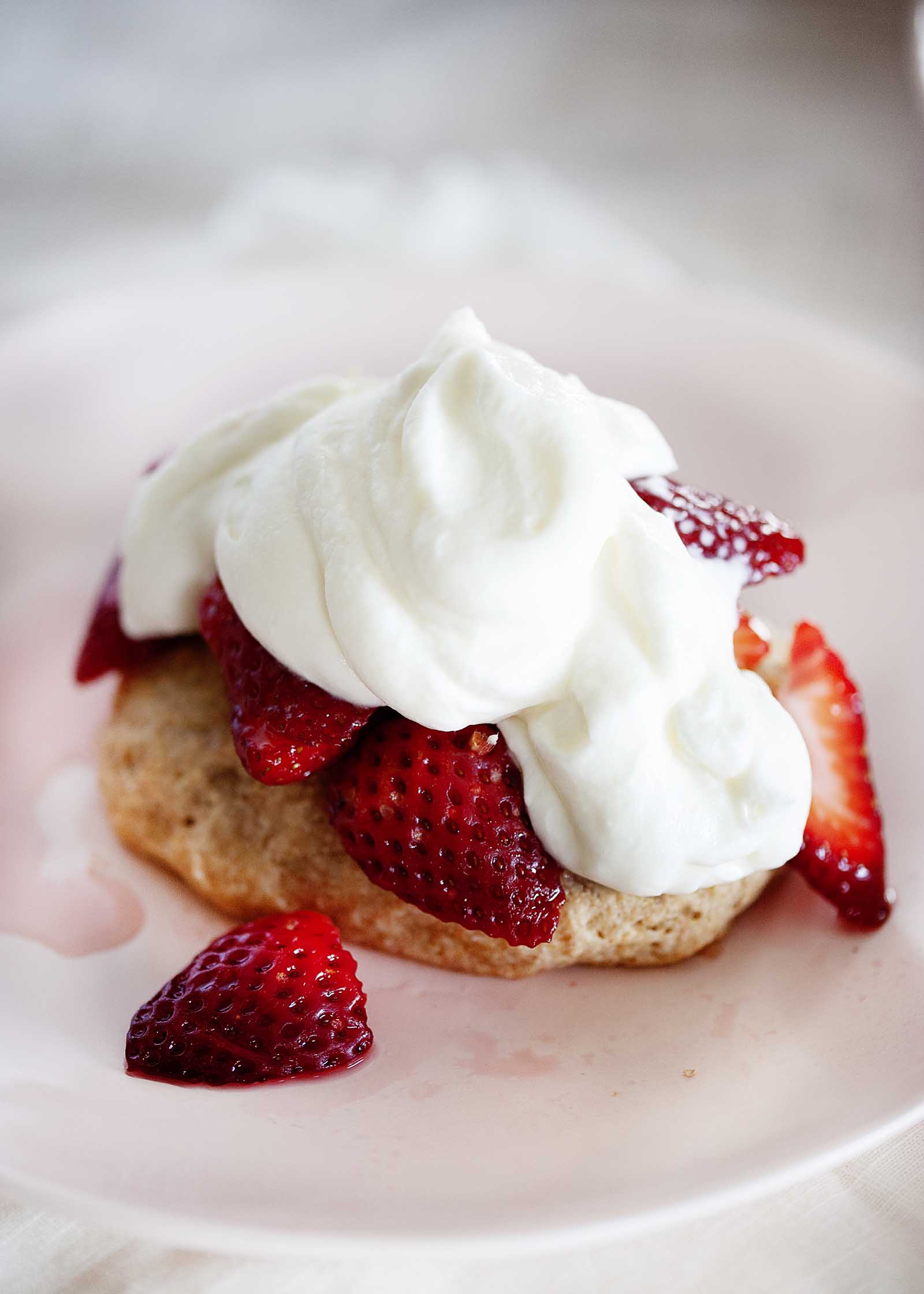Close up of open-faced strawberry shortcake with sliced strawberries and whipped yogurt topping.