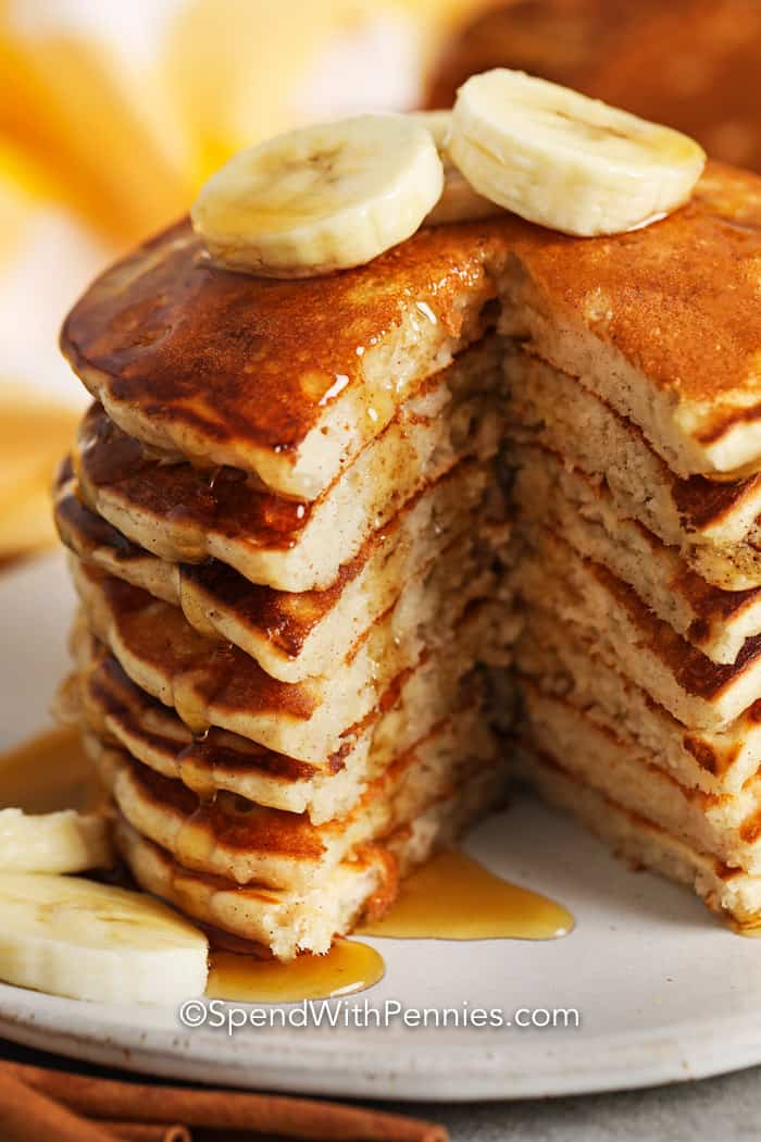 Stack of Banana Pancakes with syrup and bananas on top