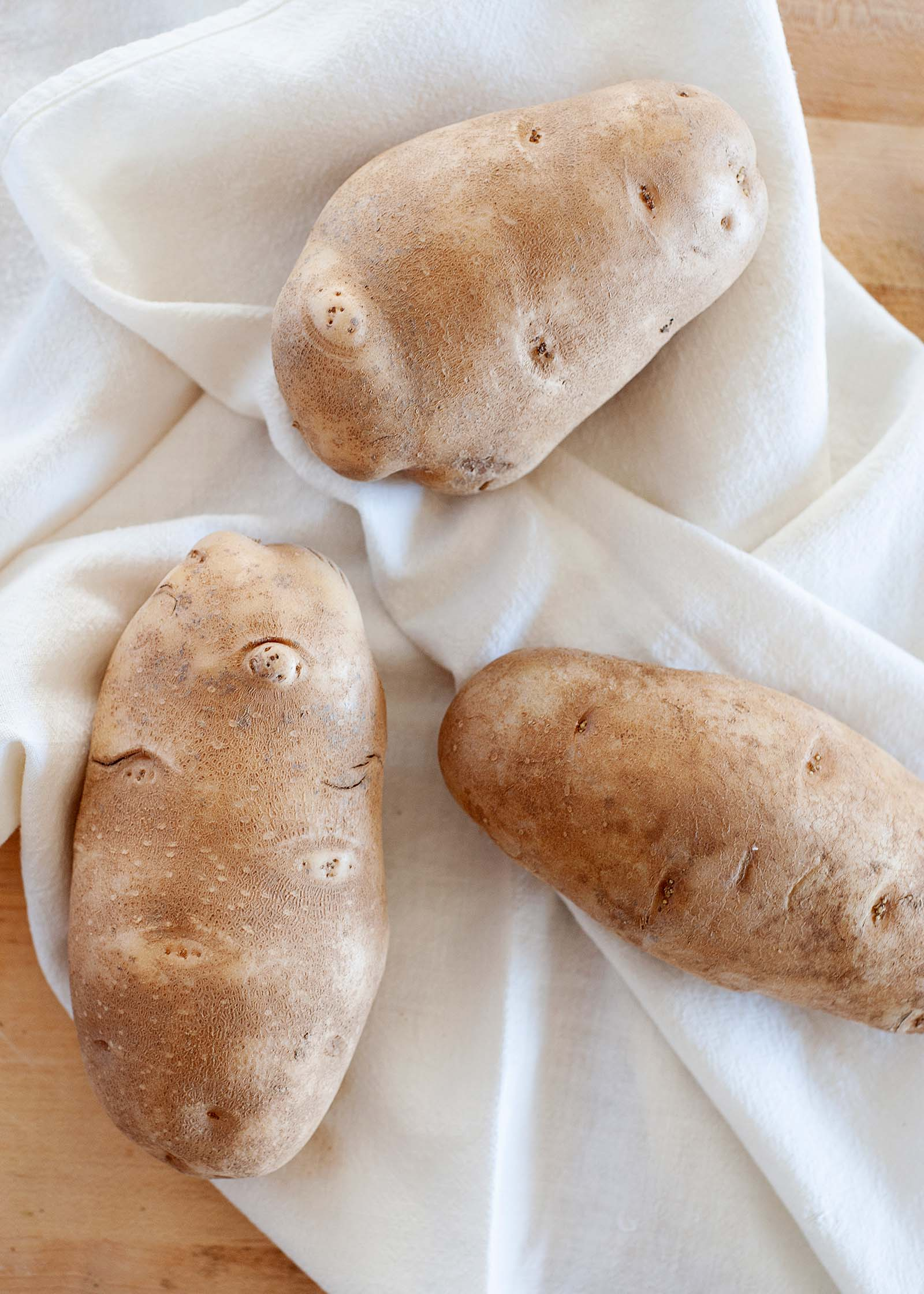 Three russett potatoes on a white linen.